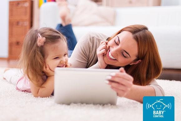 Mamá e hija sonrientes con una tablet