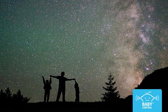 Silueta de padre con sus hijos viendo las estrellas en la naturaleza