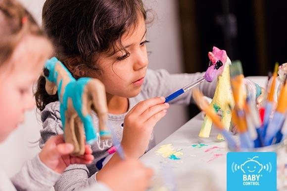 Niñas pintando un unicornio hecho de cartón