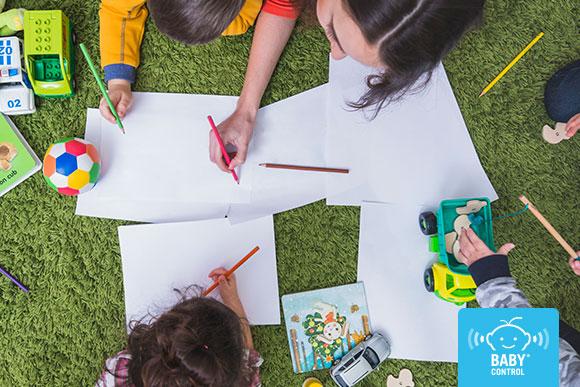Niños con mamá escribiendo en hojas sobre el césped