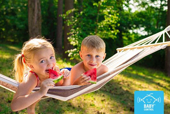 Niños comiendo sandía sobre una tumbona en verano