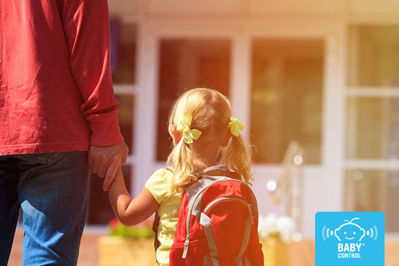 Mamá lleva a su hija de la mano hacia la escuela infantil