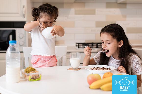 Dos niñas desayunando en la cocina