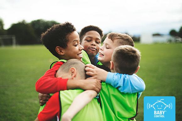 Niños que juegan al fútbol se abrazan al marcar un gol