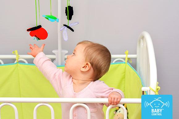 Un bebé juega en la cuna con un móvil colgante de cuna
